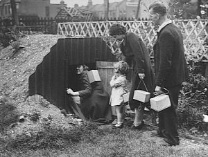 This could have been our family going into the Anderson Air raid shelter. Please note the Gas masks - the boxes we carried with us everywhere just in case there was a gas attack from the Germans.